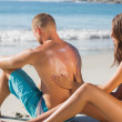 Smiling woman putting sun cream on her boyfriends back — Stock Photo #29445983