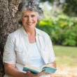 Cheerful mature woman holding book sitting on tree trunk — Stock Photo