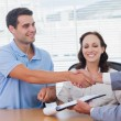 Handsome man with his wife shaking hands with estate agent — Stock Photo