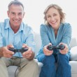 Smiling couple playing video games together on the couch — Stock Photo
