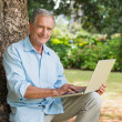 Stock Photo: Smiling old mwith laptop