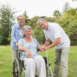 Woman sitting in wheelchair with husband and daughter — Foto Stock