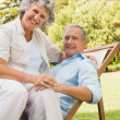 Smiling mature couple resting on sun lounger — Stock Photo