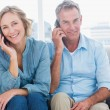 Cheerful couple on their mobile phones on the couch — Stockfoto #29447387