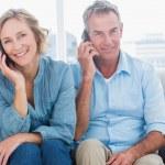 vrolijke paar op hun mobiele telefoons op de Bank — Stockfoto #29447387