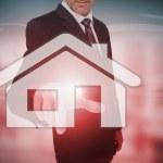 Businessman selecting futuristic house icon on touchscreen — Stock Photo