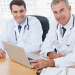 Doctors posing while working together on laptop — Stock Photo #29447467