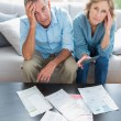Stressed couple sitting on their couch paying their bills — Stockfoto #29447703