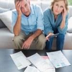 estresado pareja sentada en su sofá pagando sus cuentas — Foto de Stock   #29447703