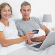 Smiling couple using their laptop to buy online — Stock Photo #29447881