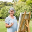 Cheerful retired woman painting on canvas — 图库照片