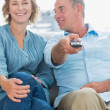 Cheerful couple sitting on the couch watching tv — Stock Photo #29448183