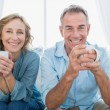Smiling middle aged couple sitting on the couch having coffee — Stock Photo