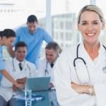 doctor Rubio sonriente posando con los colegas de fondo — Foto de Stock