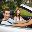 Happy couple driving in a silver convertible — Stock Photo