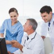 Cheerful doctors and surgeon working together on computer — Stock Photo