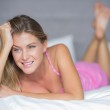 Thoughtful blonde lying on her bed smiling — Stock Photo