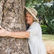 Happy older woman hugging a tree — Stock Photo