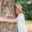 Stock Photo: Happy older womhugging tree