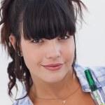 Woman holding paintbrush smiling at camera — Stock Photo #29448797