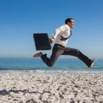Cheerful businessman jumping on the beach — Stock Photo