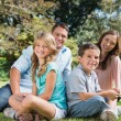 Young family sitting in a park — Stock Photo