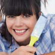 Pretty woman lying on floor holding paint brush — Stock Photo