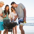 Smiling young friends having barbecue together — Stock Photo