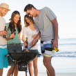 Stock Photo: Smiling young friends having barbecue together