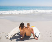 Young couple with their surfboards looking at the sea — Stock Photo