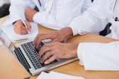 Close up on doctors hands typing on laptop — Stock Photo