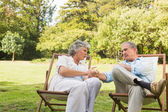 Relaxing mature couple sitting on sun loungers and talking — Stock Photo