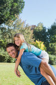 Daughter getting piggy back from dad smiling at camera — Stock Photo