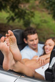 Happy couple cuddling in the backseat with focus on foot — Stock Photo