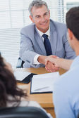 Smiling real estate agent shaking hands with his new buyer — Stock Photo