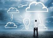 Kaufmann in anbetracht cloud computing grafiken mit glühbirne — Stockfoto