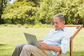 Smiling mature man using his laptop — Stock Photo