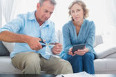 Husband cutting credit card in half with wife looking at camera — Stock Photo