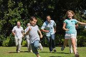 Happy multi generation family racing towards camera — Stock Photo