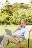 Man using laptop on sun lounger — Stock Photo