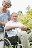Cheerful mature man in wheelchair with partner — Stock Photo