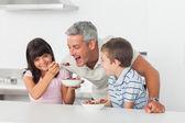 Menina dando cereal para o pai com o irmão a sorrir — Fotografia Stock