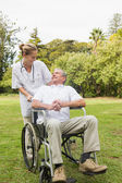 Happy man sitting in a wheelchair talking with his nurse pushing — Stock Photo