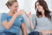 Happy women clinking their wine glasses while sitting on the sof — Stock Photo