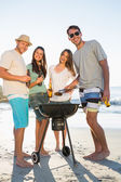 Happy friends looking at camera while having barbecue together — Stock Photo