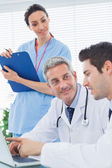 Nurse listening to doctors talking about something on their lapt — Stock Photo