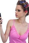Model wearing hair rollers posing looking at the phone — Stock Photo