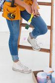 Woman holding paintbrush and wearing tool belt — Stock Photo