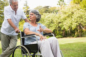 Mature woman in wheelchair speaking with partner — Stock Photo