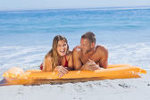 Cheerful cute couple in swimsuit taking sun — Stock Photo